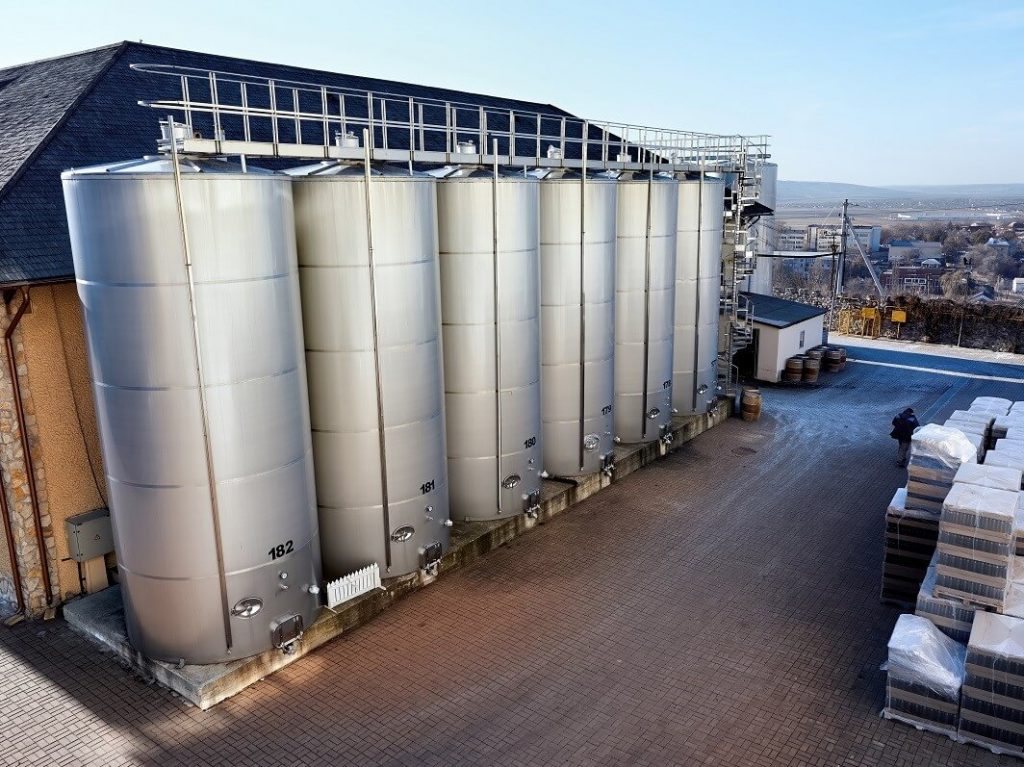 metal-wine-storage-tanks-with-dwelling-houses-background-winery